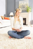 Woman Listening To MP3 Player Sitting On Rug Stock Photos