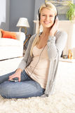 Woman Listening To MP3 Player Sitting On Rug Stock Photography
