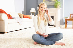 Woman Listening To MP3 Player Sitting On Sofa Stock Photography