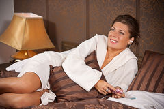 Woman listening to music. Young woman listening to music lying on a bed royalty free stock photography