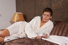 Woman listening to music. Young woman listening to music lying on a bed stock photography