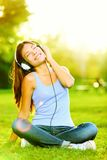 Woman listening to music. Female student girl outside in park listening to music on headphones while studying. Happy young university student of mixed Asian Royalty Free Stock Image