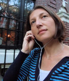 Woman Listening To Music. Woman Walks City Street Listening To Music On MP3 Player Stock Images