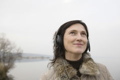 Woman Listening To Music Against Lake Royalty Free Stock Images
