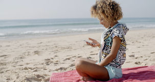Woman Listening To Music On The Beach Stock Photo