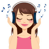 Woman Listening To Music. Beautiful brunette woman listening to music with white earphones Stock Image