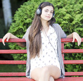 Woman listening to music. Beautiful woman listening music outdoor in the park Stock Photos
