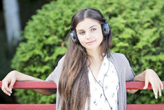 Woman listening to music. Beautiful woman listening music outdoor in the park Royalty Free Stock Images