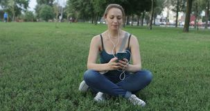 Woman listening to music on cellphone in the park. stock footage