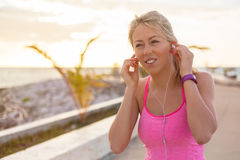Woman listening to music while doing workout outdoors Stock Images