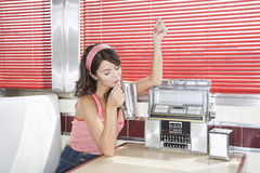 Woman Listening To Music While Drinking Shake In Diner Royalty Free Stock Photo