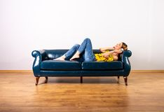 A woman listening to music and enjoying it on a sofa. A beautiful young woman in a yellow dress listening to music and enjoying it while lying on a sofa stock photo