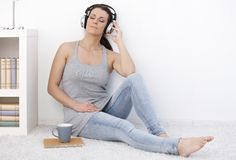Woman listening to music with eyes closed. Woman listening to music on headphones with eyes closed, sitting on floor daydreaming royalty free stock images