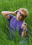 Woman listening to music with headphones. Sitting in the grass Stock Photos