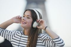 Woman listening to music on headphones. In Paris Royalty Free Stock Photos
