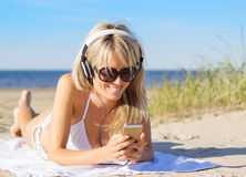 Woman listening to music on headphones on the beach Royalty Free Stock Image