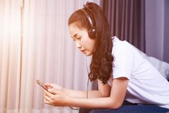 Woman listening to music in headphones with moblie on sofa at ho royalty free stock photography