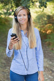 Woman listening to music with headphones at park Stock Photo