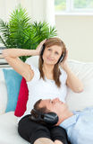 A woman listening to music with her boyfriend Stock Photography