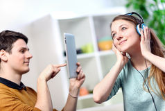 Woman listening to music husband takes pictures Stock Photography