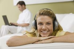 Woman Listening to Music While Husband Works Stock Photos