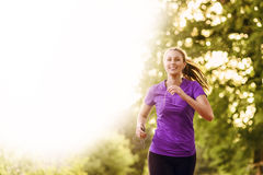Woman listening to music while jogging Stock Image
