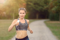 Woman listening to music while jogging Stock Photo