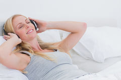 Woman listening to music while she is laid in her bed Royalty Free Stock Photos