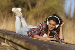 Woman listening to the music on the lake docks stock photo