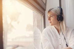 Woman listening to music, looking through the window royalty free stock photography