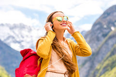 Woman listening to the music in the mountains Stock Images