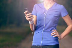 Woman listening to music on an MP3 player Royalty Free Stock Photography