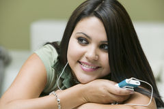 Woman Listening To Music On MP3 Player At Home Stock Images