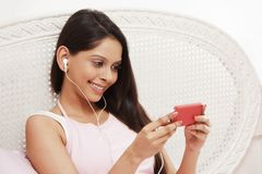Woman listening to music on a mp3 player Royalty Free Stock Photography