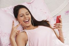 Woman listening to music on a mp3 player Stock Images