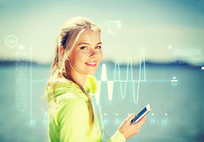 Woman listening to music outdoors. Fitness and lifestyle concept - woman doing sports and listening to music outdoors Royalty Free Stock Photography