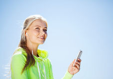 Woman listening to music outdoors. Sport and lifestyle concept - woman doing sports and listening to music outdoors Stock Photography