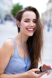 Woman listening to music outdoors Stock Image
