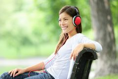 Woman listening to music in park royalty free stock image
