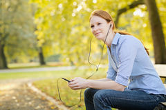 Woman Listening to Music in a Park Royalty Free Stock Photos