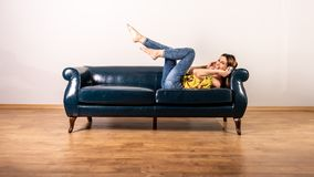 A woman listening to music while posing on a sofa. A beautiful happy young woman in a yellow dress listening to music and enjoying it while posing on a sofa royalty free stock photography