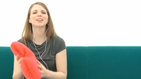Woman listening to music. Pretty Woman listening to music and cuddling with a heart pillow stock footage