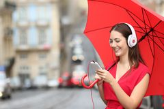 Woman listening to music a rainy day in the street. Happy woman listening to music with phone and headphones in a rainy day in the street Stock Image