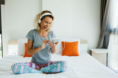 Woman listening to music in room Stock Photography