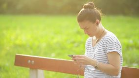 Woman listening to the music from a smart phone with headphones in a park, beautiful woman using smartphone with stock video footage