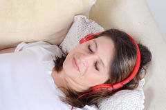 Woman listening to music on the sofa. Royalty Free Stock Images