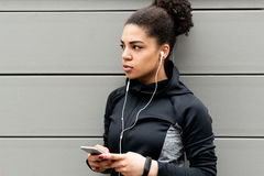 Woman listening to music while standing at wall. Outside Royalty Free Stock Photo
