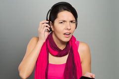 Woman listening to music struggling to hear. Beautiful young woman in a stylish pink outfit with a scarf listening to music struggling to hear something that is Stock Photos