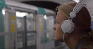 Woman listening to music in subway stock video