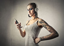 Woman listening to music. Tattooed young woman listening to music Stock Images